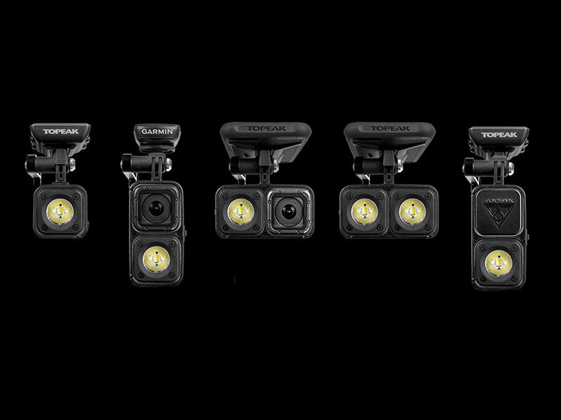 Foto frontale della selezione dei nuovi prodotti Topeak. Le luci da bicicletta montabili sul manubrio sono disposte in orizzontale una dopo l'altra con la luce accesa.